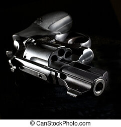 nighttime gun - revolver that is starkly lit on a black...