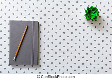 Covered grey diary at table - Pencil is on closed notebook....