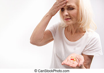 Frowning old woman keeping medications - Mature lady is...