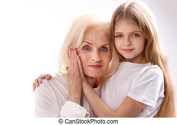 Mature woman near her granddaughter - Old lady is beside...