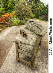 Unusual curved park bench with low point of view in Autumn Fall