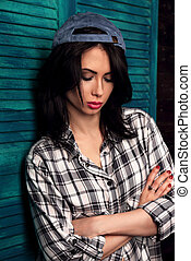 Beautiful makeup teen girl in trendy black and white checkered shirt and blue summer cap thinking on blue wooden background with folded arms looking down. Short hairstyle.
