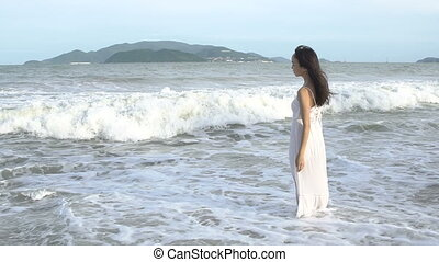 Woman walking on beach in summer. Happy multiracial Asian girl going to sea.