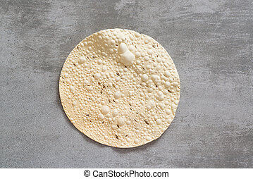 Papadam, a traditional indian snack on a concrete background