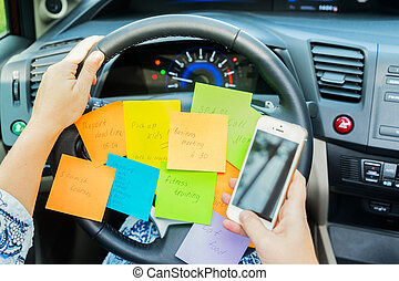 To do list in a car on driving wheel and hand holding phone...