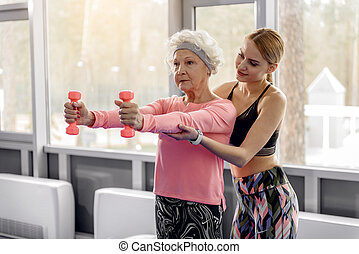 Serene grandmother making exercises with dumbbell - Calm...