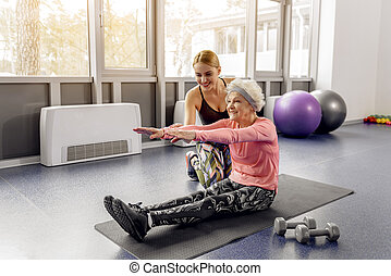 Happy female helping beaming retiree making workout -...