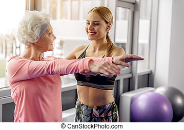 Smiling grandmother dealing with coach in gym - You do all...