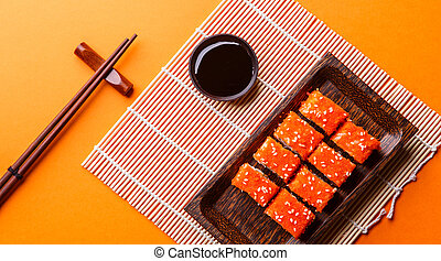 Photo of sushi on plate at table with chopsticks