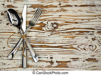 Crossed fork table knife and spoon on old wooden boards