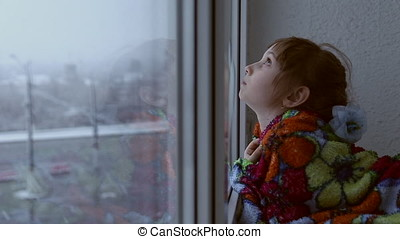 Girl looking out the window at the snowfall