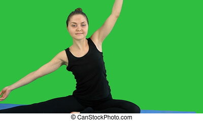 Fitness woman stretching her body doing pilates on a Green...