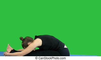 Young woman stretching leg on mat, practicing yoga on a Green Screen, Chroma Key