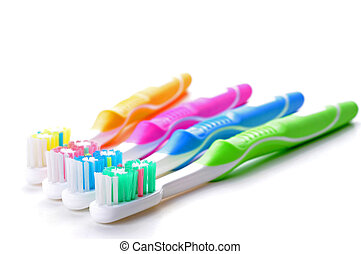 Toothbrushes - Four very colorful toothbrushes on a white...