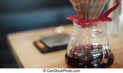 Barista prepares Pour Over, Chemex Dripping hot fresh coffee, filtered. The flask is weighed.