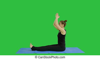 Young girl doing stretching exercises on a Green Screen,...
