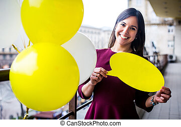 Smiling young woman holding a yellow plate in the hands