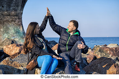 Young friends are giving high five and smiling while sitting on the rocky beach