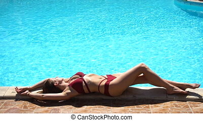 Woman lying near summer swimming pool