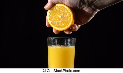 People's hand squeeze the orange fresh juice in glass, slow...