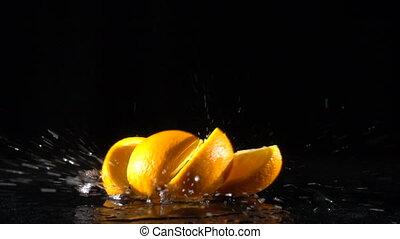 falling orange fruit slices on black background, slow motion