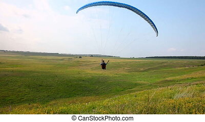 Paraplane. - Paraglider lands on the lawn near the village.