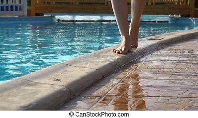 Woman in summer walking near swimming pool in slow motion