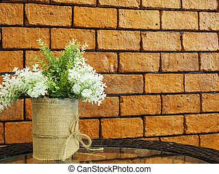 Decorated artificial flowers in flowerpot on glass table with red brick wall background.