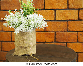 Decorated artificial flowers in flowerpot on wooden table with red brick wall background.