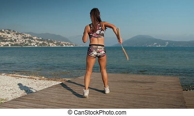 The female athlete trains with nunchaku on the timber...