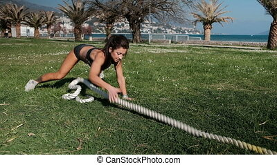 Woman in sportswear training pulls thick cable, hawser...