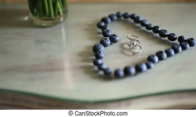 Wedding rings in a heart of a blueberry on a table, next to a br