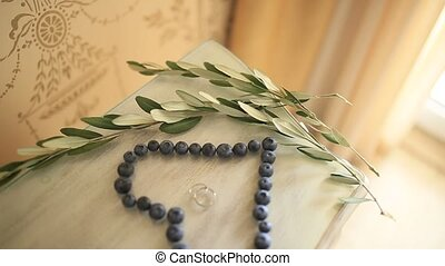 Wedding rings in a heart of a blueberry on a table, next to...