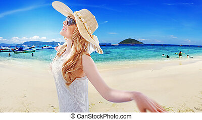 Portrait of a beautiful blonde resting on the beach -...
