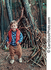 Cute little boy building a wooden hut - Cute little boy...