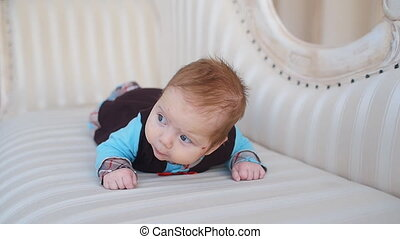 Infant lies on the sofa - Cute happy Infant lies on the sofa
