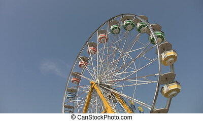 Ferris wheel. - Big ferris wheel with multi-coloured cars at...