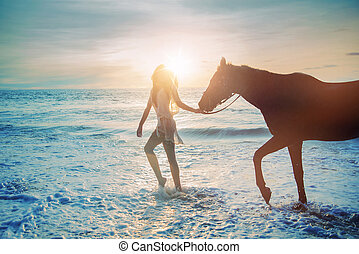 Pretty lady walking with the majestic horse