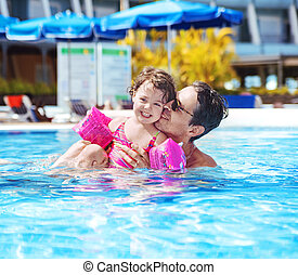 Handsome dad swimming with a cute daughter