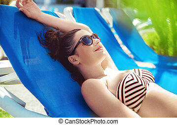 Brunette lady relaxing at the hotel's swimming pool -...