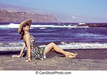 Attractive young lady sitting on the beach - Attractive...