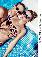 Attractive couple resting by the swimming pool