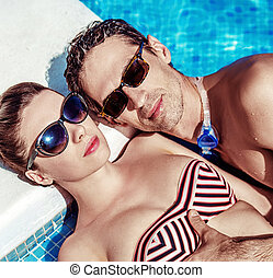 Attractive couple relaxing by the swimming pool