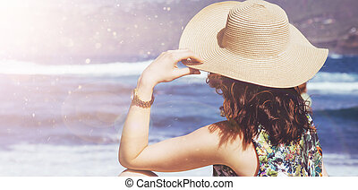 Young, relaxed lady looking at the ocean