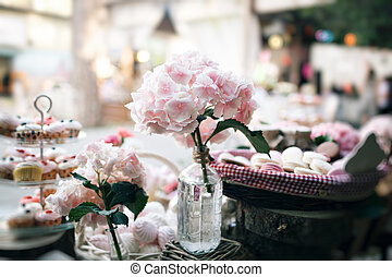 Dessert table for a party. Ombre cake, cupcakes, sweetness and flowers. selective focus