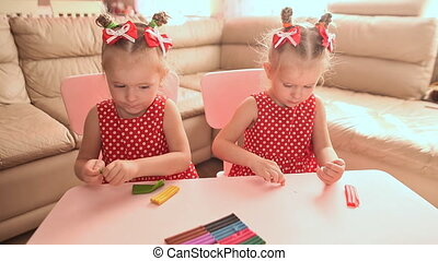 Two cute little twin sisters together are engaged in modeling with multi-colored plasticine.