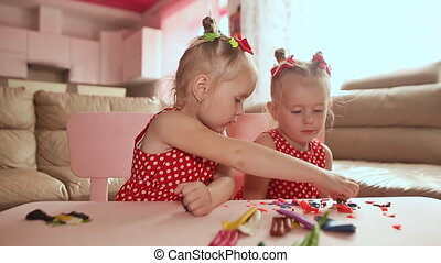 Two cute little sisters, with pleasure together with colorful modeling. Creative children at home. Children play with plasticine or dough.