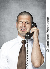 businessman crying while talking on the phone