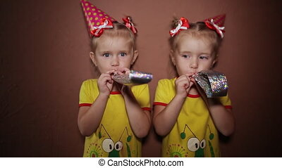 It's a holiday. Two charming little twin sisters in red dresses and cone-shaped caps on their heads are blowing into unfolding tubes.