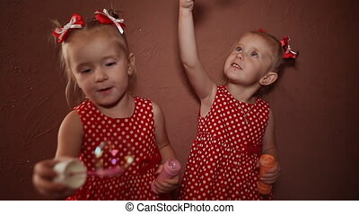 Two beautiful twin sisters in delightful red dresses blow...